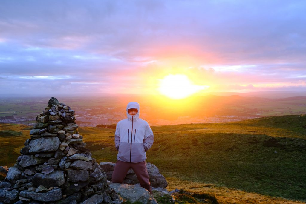 Man on mountain standing in front of incredible sunset