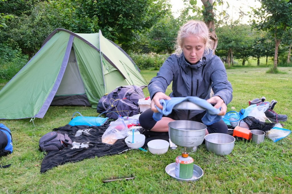 Girl camping in tent and cooking a camping meal on a camping stove