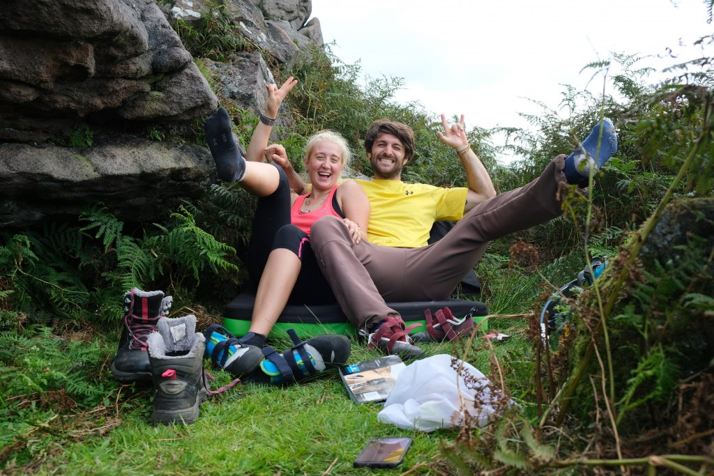Couple sitting of climbing crash pad in countryside