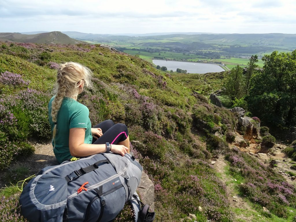 Girl backpacking above lake view