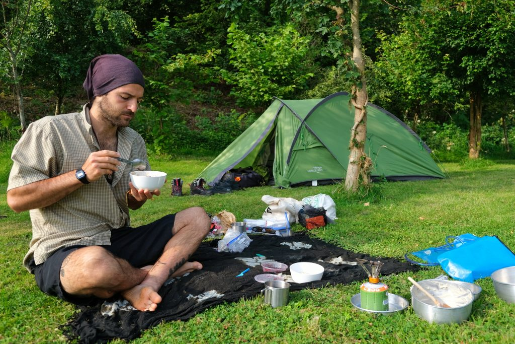Man eating breakfast outside practising leave no trace camping