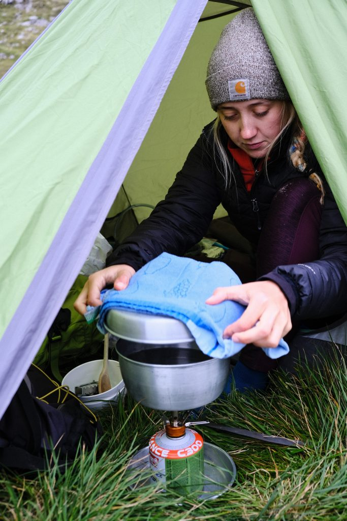 Girl cooking whilst wild camping