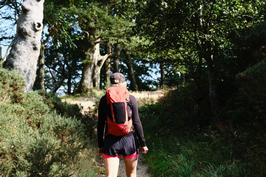Women wearing a sustainable climbing rucksack hiking through woodland