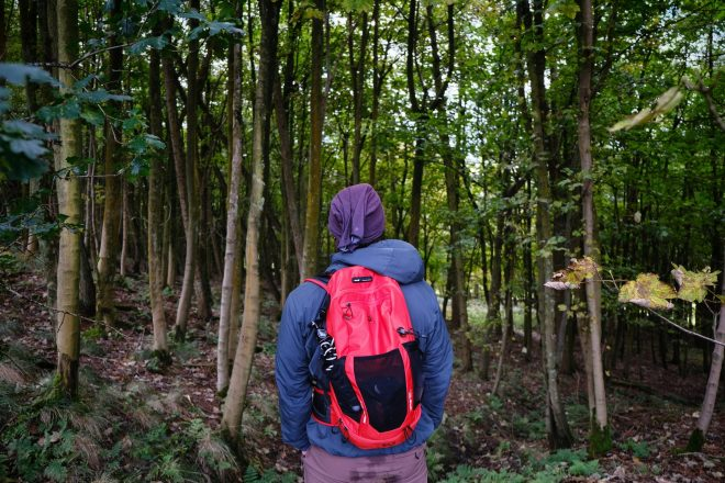 Man with sustainable backpack hiking through woods