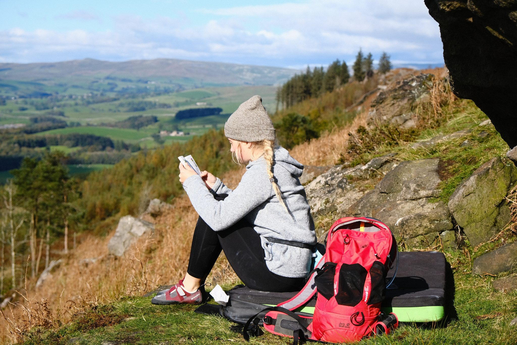 Female rock climber sitting on a climbing mat