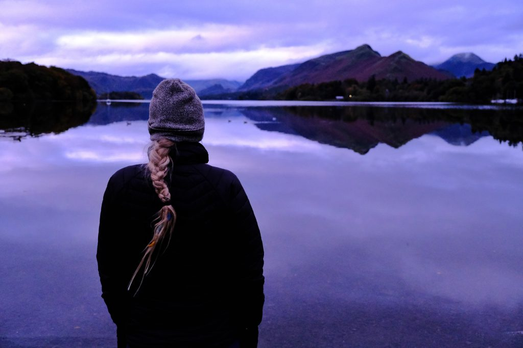 Girl standing by lake watching the sunrise