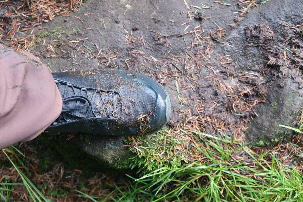 Muddy vegan hiking boot on trail