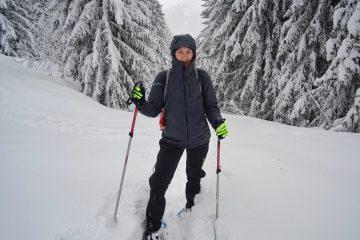 Girl snowshoeing through woods wearing a vegan winter coat