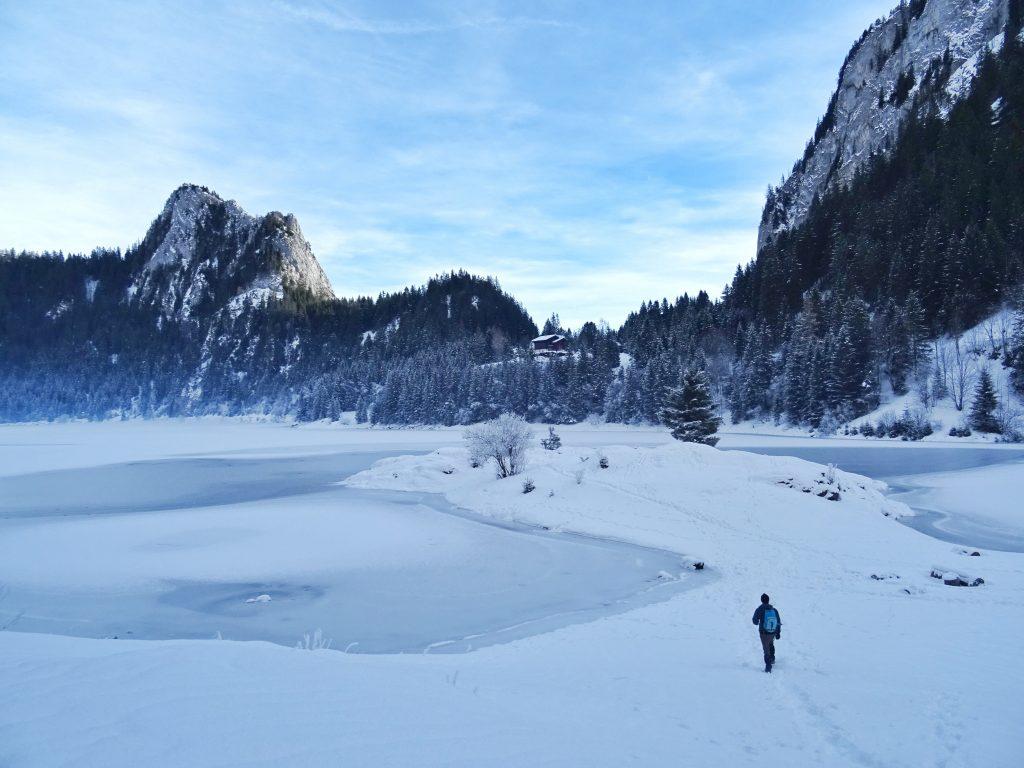 Man walking beside frozen lake wearing a vegan insulated jacket
