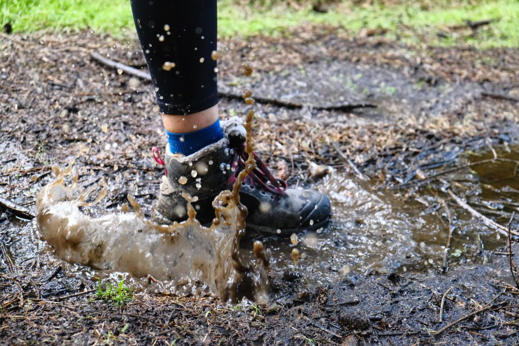 Girl wearing waterproof hiking boots and stepping into puddle