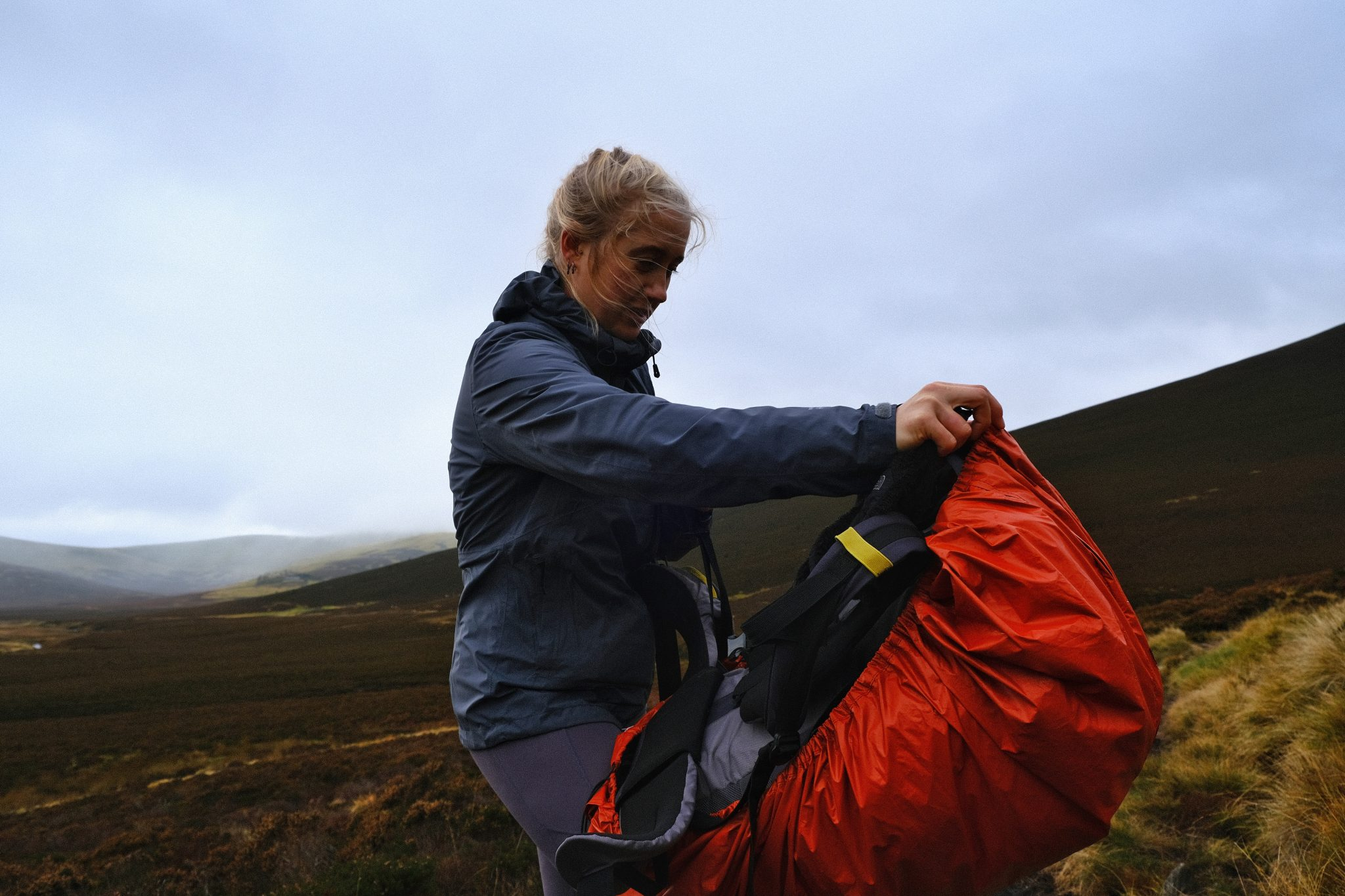 Girl backpacker putting on waterproof bag cover