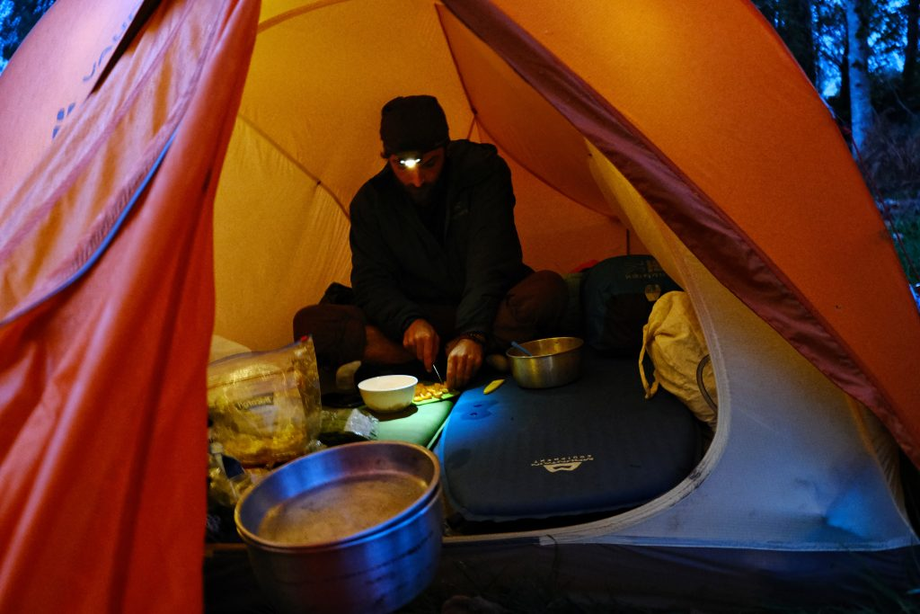 Man cooking in a Vaude tent