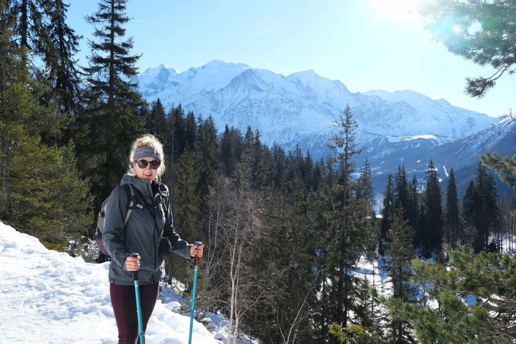 Girl snowshoeing through the French Alps wearing winter hiking clothes with vegan puffer jacket
