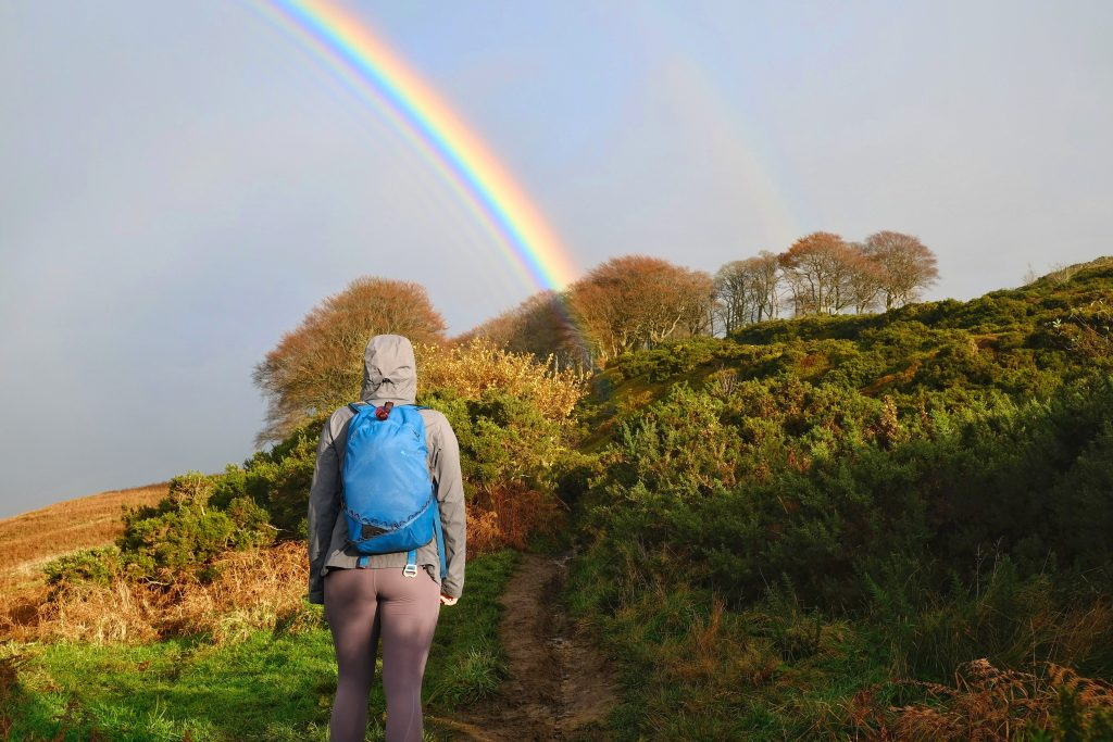 Girl hiking under rainbow