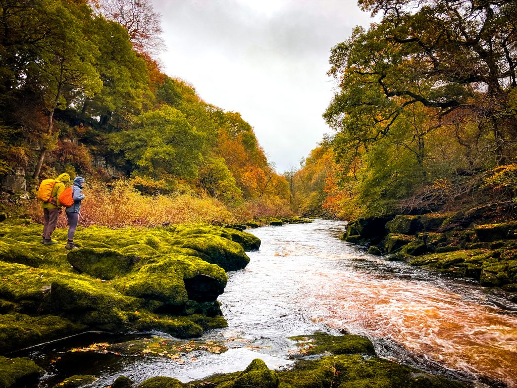 Couple hiking in the rain beside river