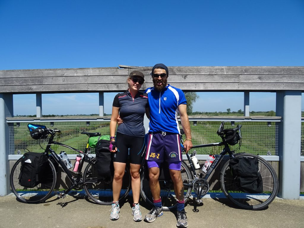 Couple standing in front of bike on a bike tour