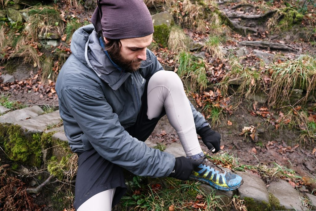 Trail running lacing up a pair of Inov-8 Terraultra G 270