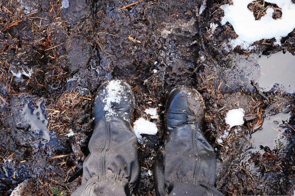 A pair of winter hiking boots with gaiters, standing in mud