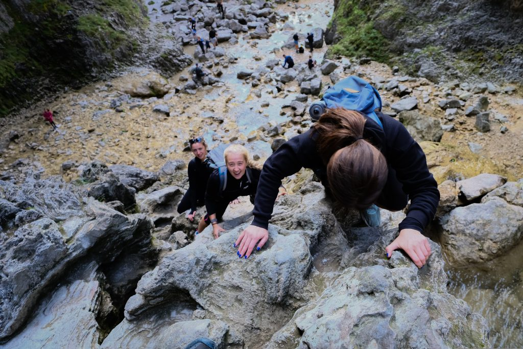 Hikers climbing up a rockface