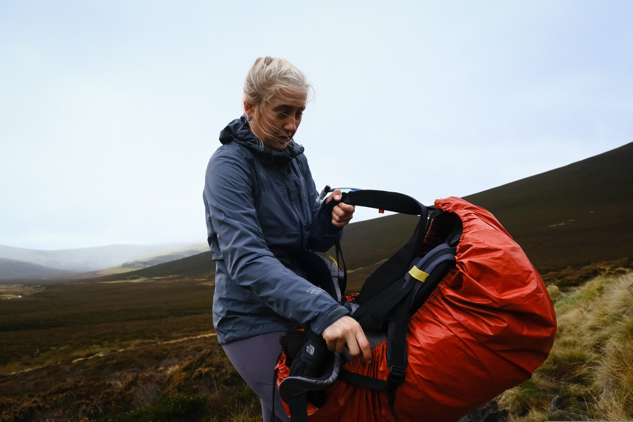 Girl putting on a waterproof and a waterproof rucksack cover