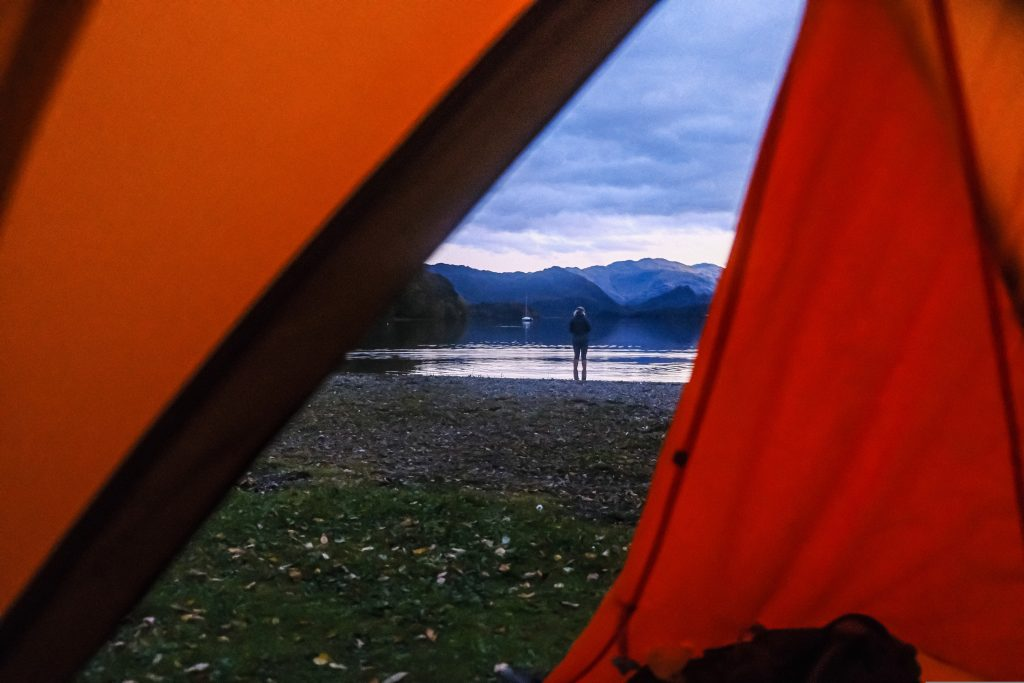 Girl standing outside of backpacking tent