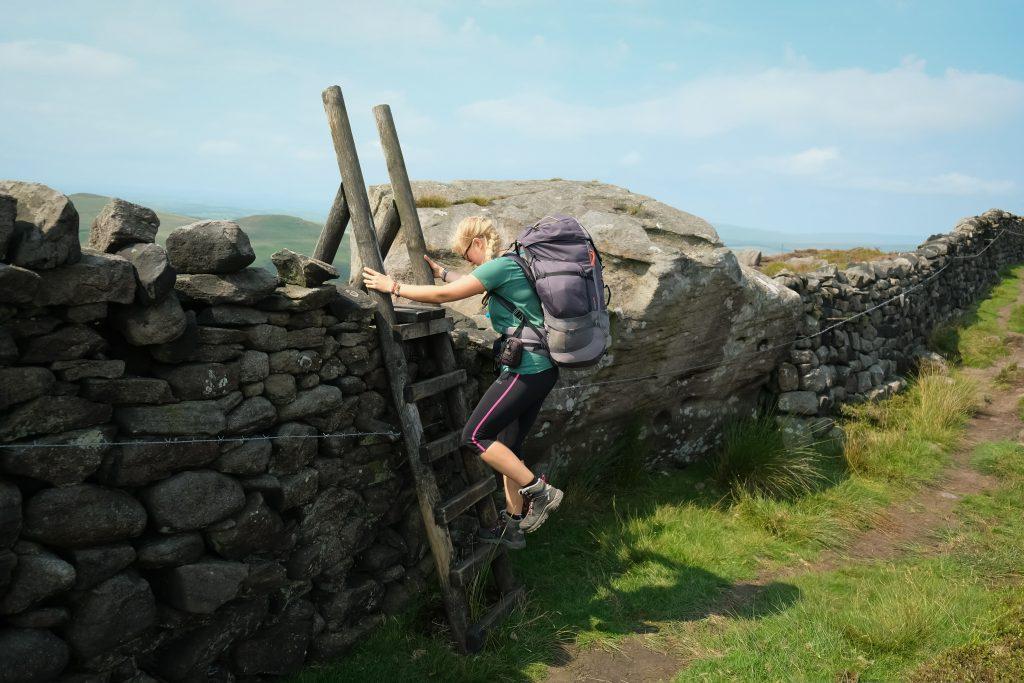 Women hiking over turnstyle
