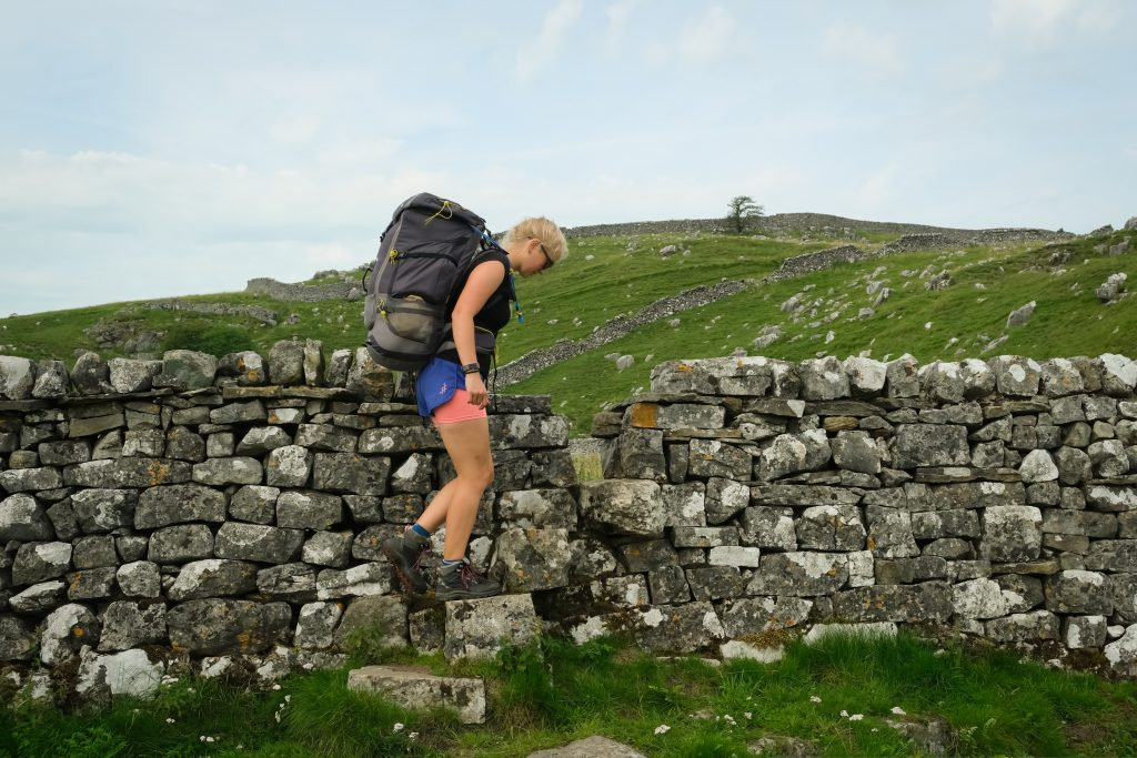 Woman hiking in shorts over wall
