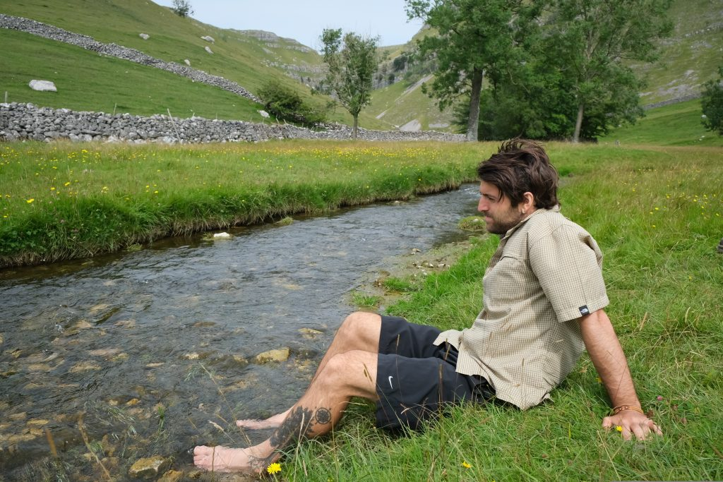 Backpacker cooling feet in river