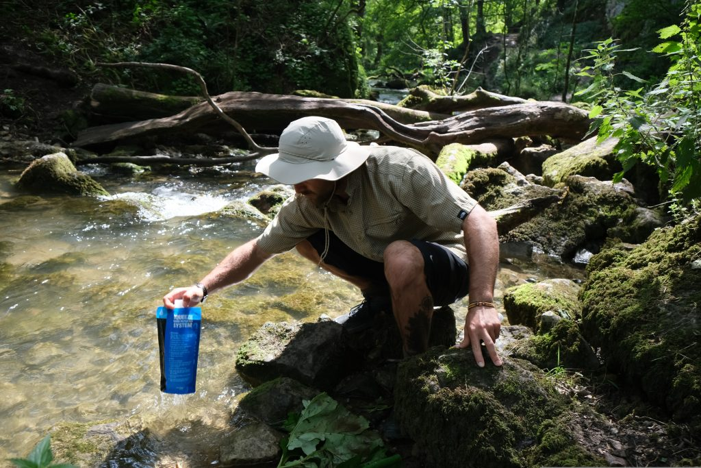 Backpacker refiling water from stream