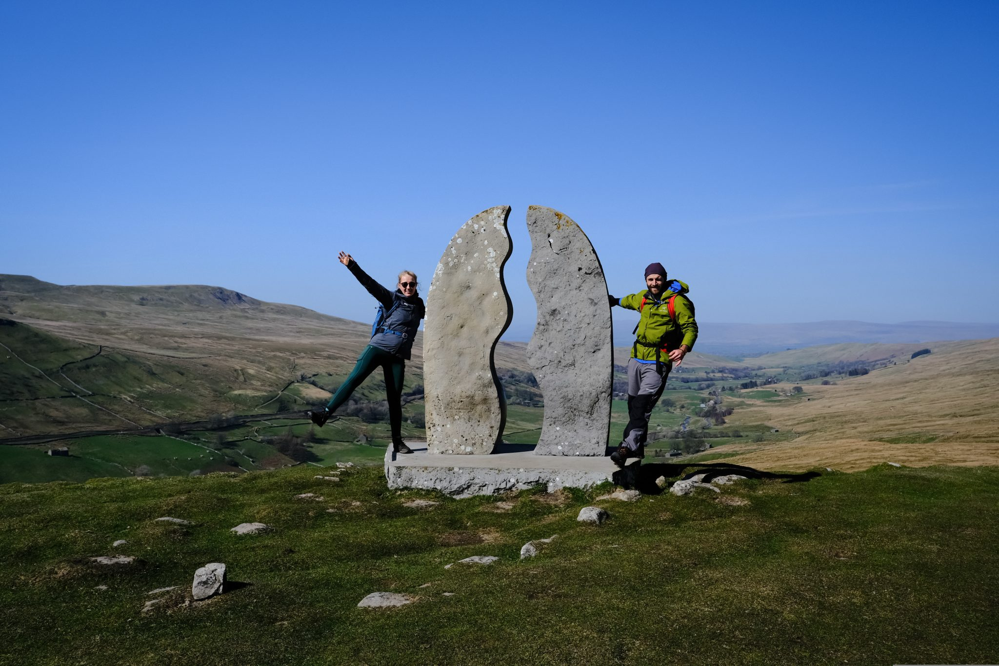 Two hikers standard by art installation