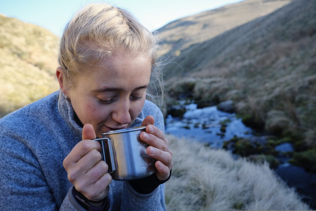 hiker drinking tea by a river