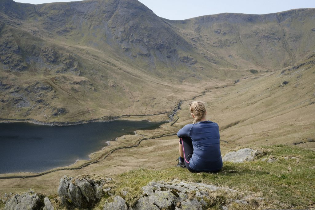 Girl sitting by a reservoir in the lake district
