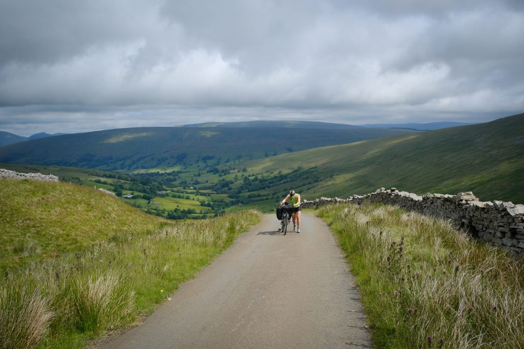 Female cyclist going up hill