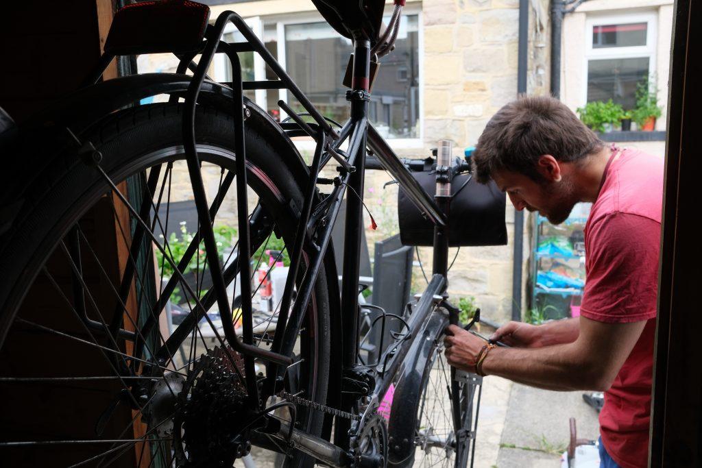 Man making bike repairs to start an adventure