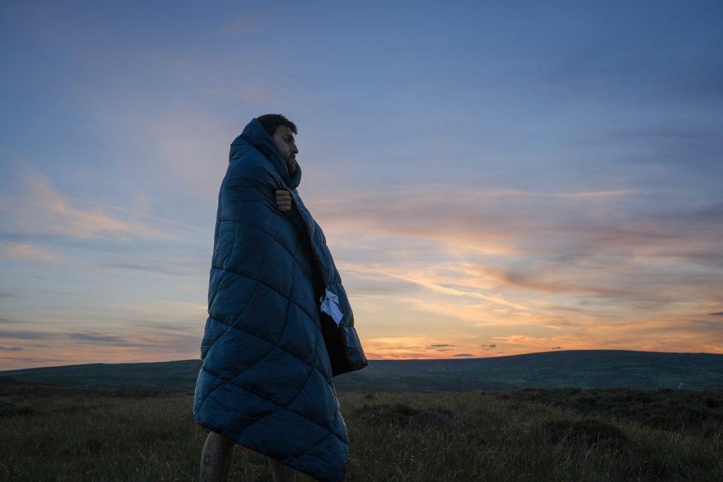 Man in Rumpl camping quilt