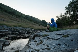 Man on his own adventure sitting by river eating a camping meal